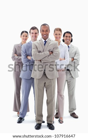 Smiling business team crossing their arms against white background - stock photo