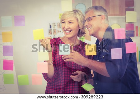 Smiling business team pointing post its on the wall at office - stock photo
