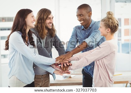 Smiling business team putting their hands together at office - stock photo