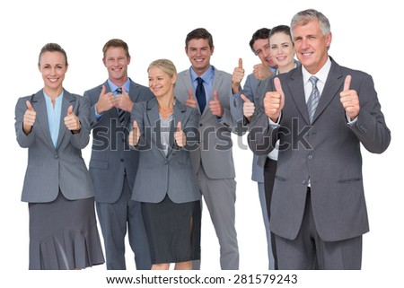 Smiling business team showing thumbs up on white background - stock photo