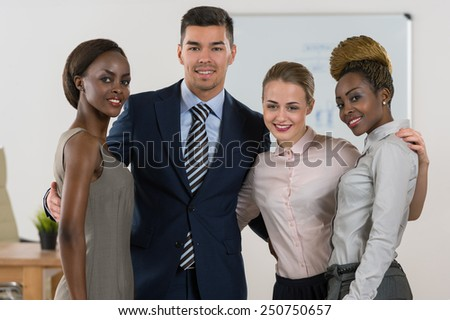 Smiling business team standing together at office - stock photo