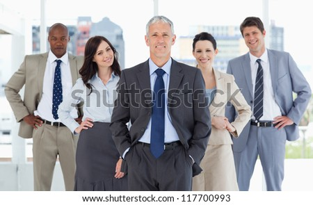 Smiling business team standing upright with their hands on their hips - stock photo