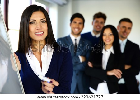 Smiling business team with flip board in office - stock photo