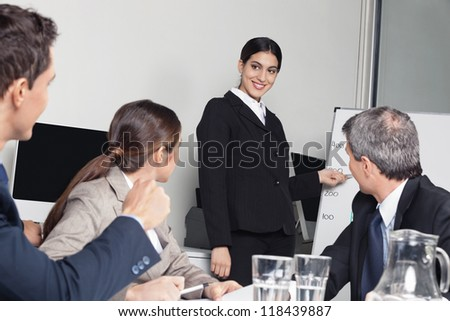 Smiling business woman giving a sales presentation for her team in the office - stock photo