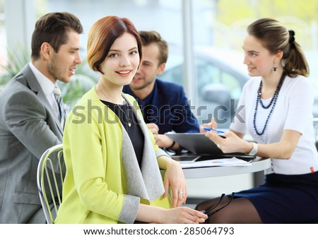 Smiling business woman in foreground  and her co-workers discussing business matters in the background - stock photo