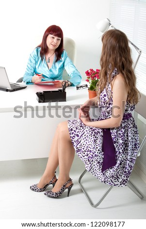 smiling business woman interviewing a young girl - stock photo