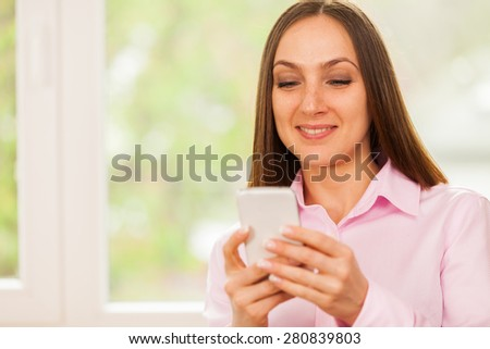 Smiling business woman is typing a message on her phone - stock photo