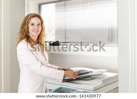 Smiling business woman operating photocopy machine in office - stock photo