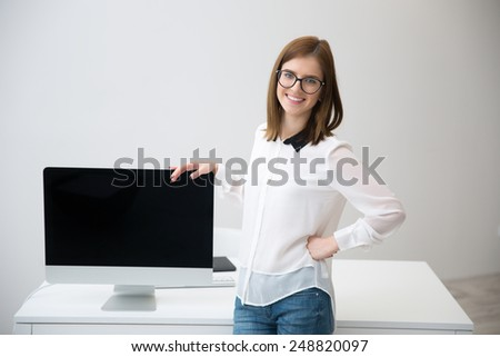 Smiling business woman presenting blank monitor screen - stock photo