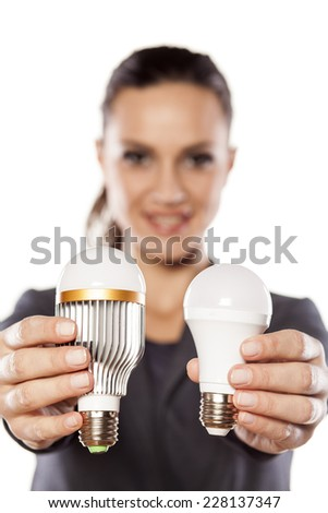 smiling business woman showing a new generation of LED bulbs - stock photo