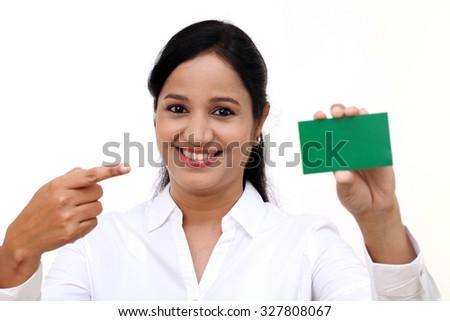 Smiling business woman showing blank business card - stock photo