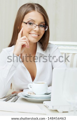 Smiling business woman sitting at table, close-up - stock photo