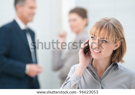 Smiling business woman talking on mobile phone at office - stock photo