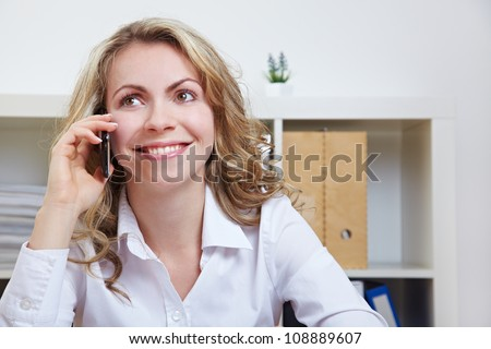 Smiling business woman using smartphone to make a call - stock photo