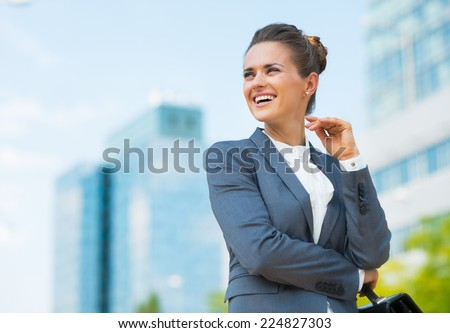 Smiling business woman with briefcase in office district looking on copy space - stock photo