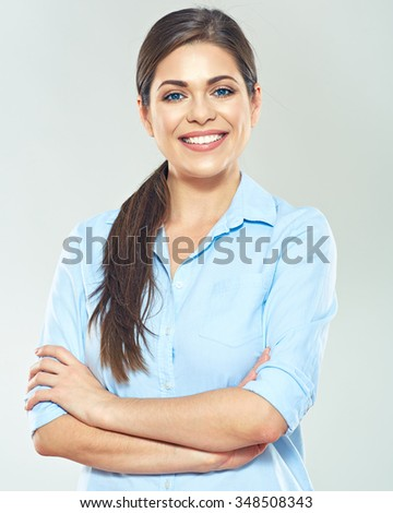 Smiling business woman with crossed arms standing against gray studio isolated background. - stock photo