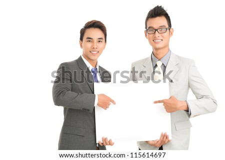 Smiling business workers pointing at a blank banner demanding attention - stock photo