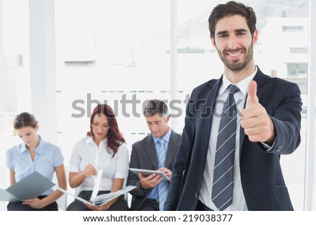 Smiling businessman and his co-workers sitting behind - stock photo