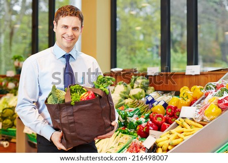 Smiling businessman buying bag of fresh vegetables in organic food store - stock photo
