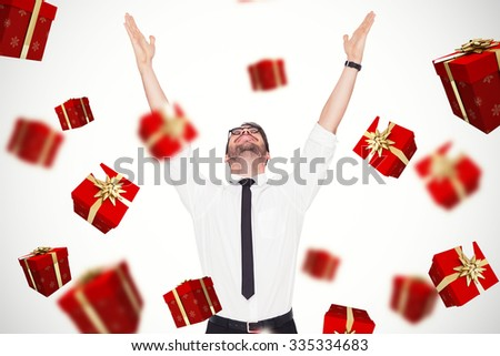 Smiling businessman cheering with his hands up against red and gold presents - stock photo