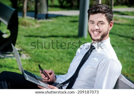 Smiling businessman. Confident and successful businessman talking on mobile phone and holding a laptop and sitting on his lap in a park on a bench. Successful businessman in formal attire. - stock photo
