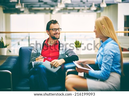 Smiling businessman discussing plans or ideas with his secretary in office  - stock photo