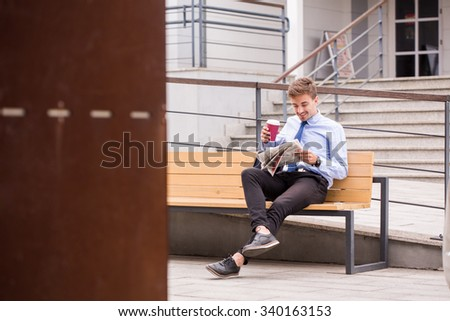 Smiling businessman drinking coffee and reading newspaper - stock photo