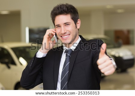 Smiling businessman giving thumbs up on phone at new car showroom - stock photo