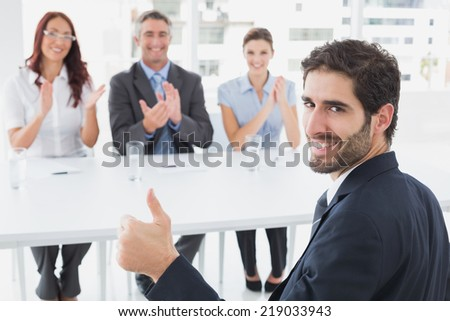 Smiling businessman giving thumbs up with co-workers - stock photo