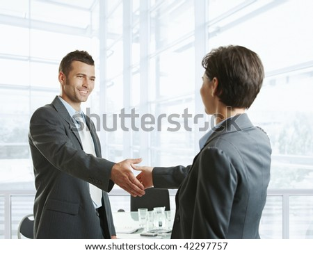 Smiling businessman greeting businesswoman with handshake before meeting. - stock photo