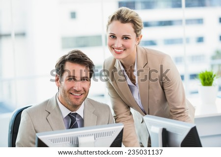 Smiling businessman helping his colleague at a computer at work - stock photo