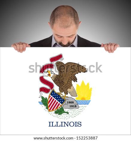 Smiling businessman holding a big card, flag of Illinois, isolated on white - stock photo