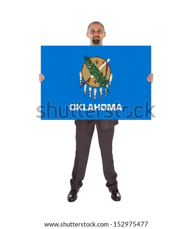 Smiling businessman holding a big card, flag of Oklahoma, isolated on white - stock photo