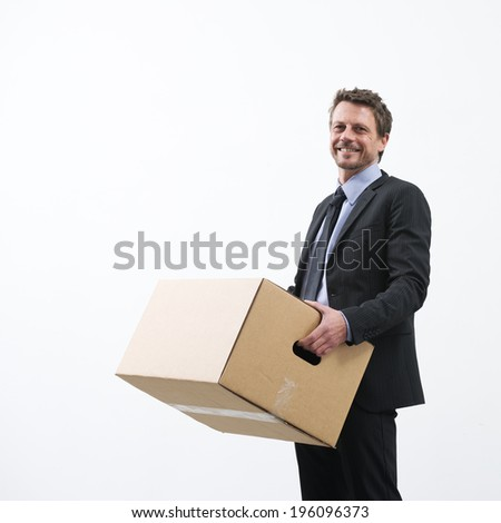 Smiling businessman holding a cardboard box and standing into an empty new office. - stock photo
