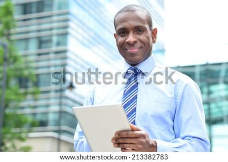 Smiling businessman holding digital tablet - stock photo