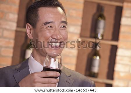Smiling Businessman Holding Wine Glass - stock photo