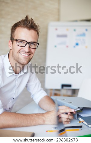 Smiling businessman in eyeglasses looking at camera in office - stock photo