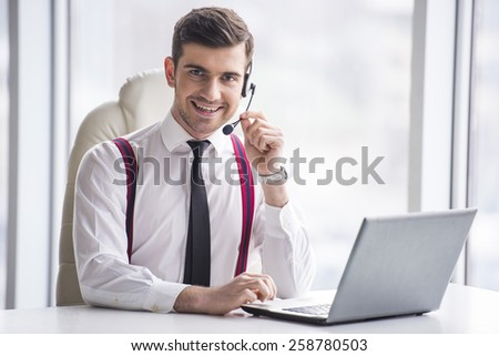 Smiling businessman is taking a call on a headset as he deals with queries at the customer support call centre. - stock photo