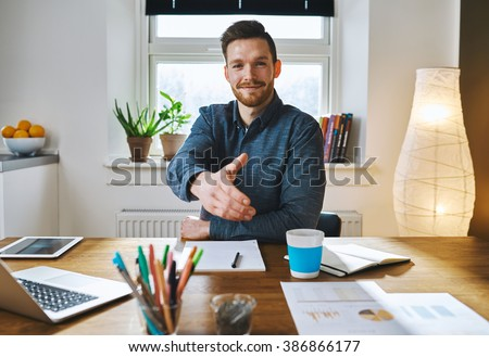 Smiling businessman leaning across his desk offering his hand in greeting, to close a deal, in partnership or congratulations - stock photo