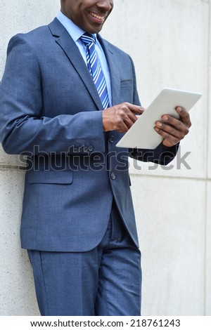 Smiling businessman leaning on wall using tablet - stock photo