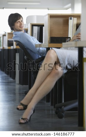 Smiling businessman looking at female colleague's bare legs in office - stock photo