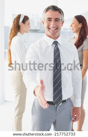 Smiling businessman offering a handshake at work - stock photo