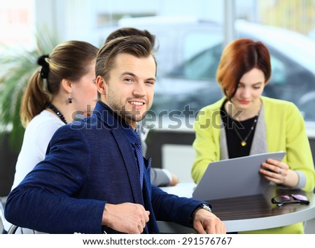 Smiling businessman on the foreground and his coworkers discussing business - stock photo