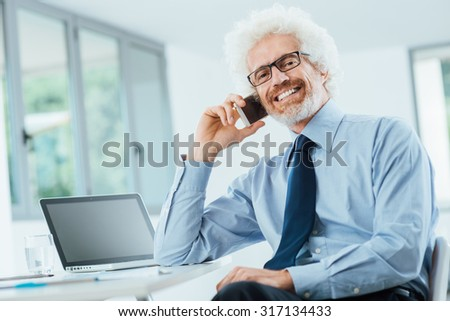 Smiling businessman on the phone sitting at office desk, looking at camera, interior on background - stock photo