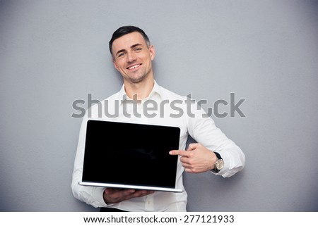 Smiling businessman pointing finger on blank laptop screen over gray background. Looking at camera - stock photo