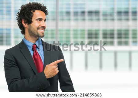 Smiling businessman pointing his finger to the copy-space - stock photo