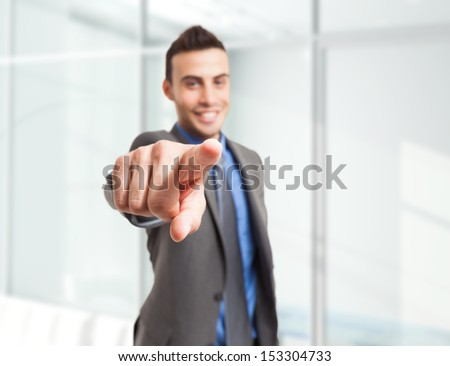 Smiling businessman pointing his finger to you - stock photo