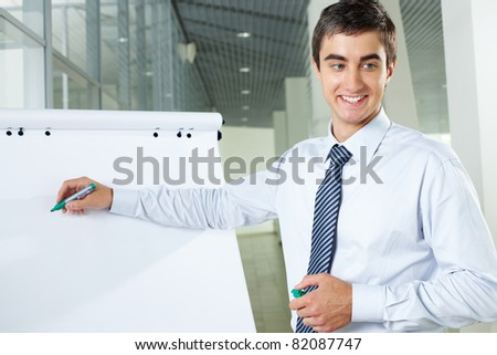 Smiling businessman presenting new project to partners on a whiteboard - stock photo