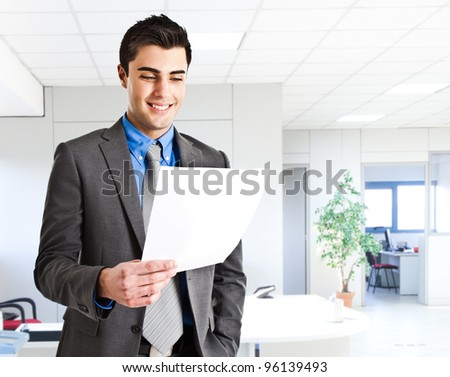 Smiling businessman reading a document - stock photo