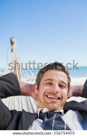 Smiling businessman relaxing in hammock looking at camera on sunny day - stock photo